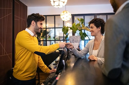 Business Woman Getting Key Card From Hotel Receptionist