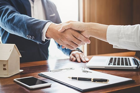 Real Estate Agent and Customers Shaking Hands Together Celebrating Finished Contract About Home Insurance and Investment Loan